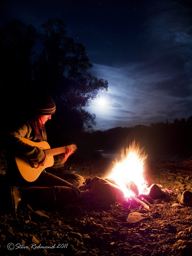 Guitar player at campfire